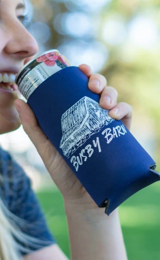 woman drinking from a can that is covered with a custom printed drink koozie