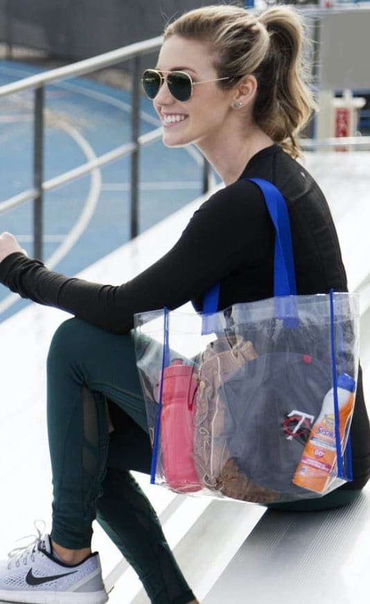woman sitting outside a race track with a clear plastic tote bag